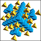 Small square outline surrounding geometric crystal structure showing clusters of yellow and blue tetragonal shapes.